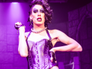 Awash in purple lighting, Alaska as Dr. Frank-N-Furter.
